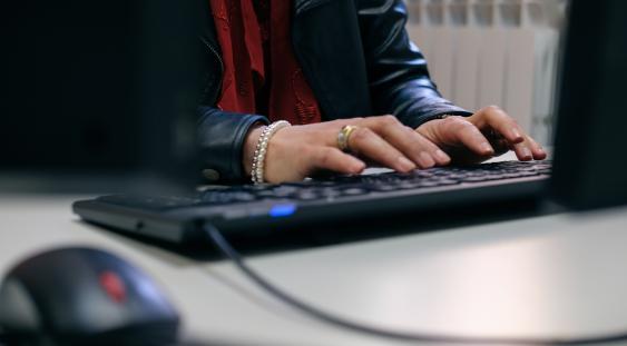 Impiegato al lavoro: particolare mani al lavoro su tastiera del pc